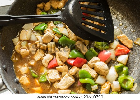stir fried chicken and capsicum in the pan : thai food. Ingredient is chicken, onions, sweet peppers mix together