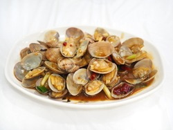 Stir fried Clams with roasted chili paste in white dish on the white table.