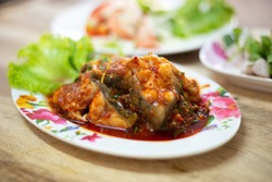 Stir-fried deep fried fish (Asian redtail catfish) with red curry paste. Thai healthy asian food from fish cooked.