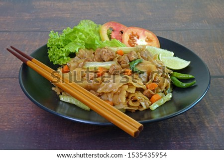 Stir fried flat noodle with black soy sauce, tofu, carrots and green vegetables. Vegetarian food for vegetarian festival. Famous Thai-Chinese cuisine.