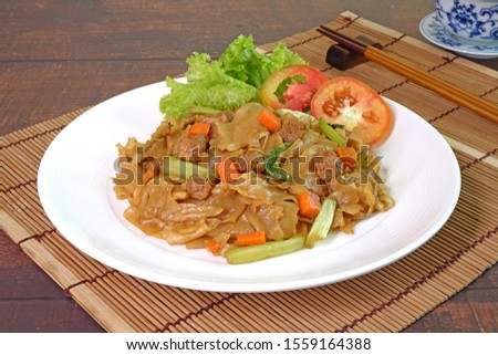 Stir fried flat noodle with black soy sauce, tofu, carrots and green vegetables. Vegetarian food for vegetarian festival. Thai style stir fry flat noodle. (Pad See Ew) Selective focus with copy space