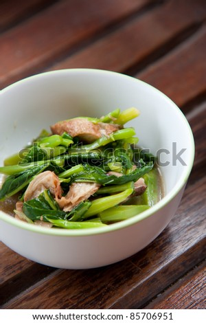 Stir-fried mix colorful vegetables and herb in white round bowl on wood pattern background