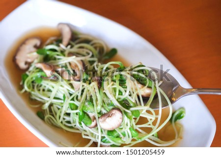 stir fried pea sprout with mushroom on the white plate vegetarian menu for vegetarian festival