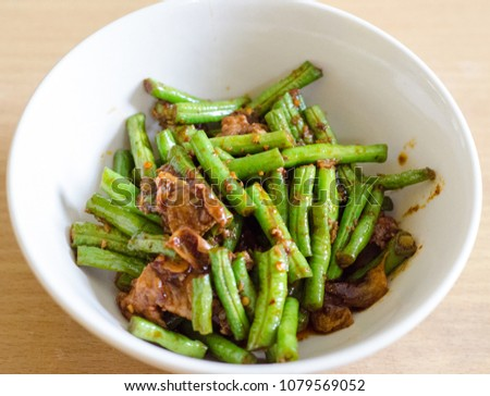 Stir fried pork belly with bean and red curry paste #1079569052
