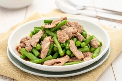 Stir-fried pork with yardlong beans or cowpeas (Vigna unguiculata) served on the white plate. Its cooking way presents that Thai food often does reflect the Chinese cuisine.