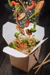 Stir-fried rice in box. Falling down ingredients such as chicken meat, broccoli, pepper, lettuce, asparagus, rice and sesame seeds. Asian food delivery.