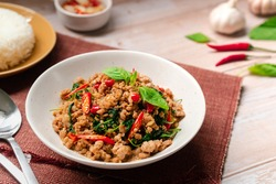 Stir-fried Thai basil with pork which   famous Thai food is hot and spicy dish  serving with rice and fish sauce on a wooden table