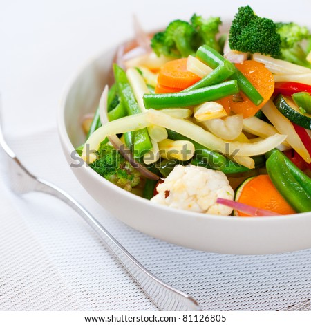 Stir-fried vegetables in a bowl. Mixed vegetable salad with green and white bean, red pepper, green peas, broccoli, carrot and cauliflower. Concept for a tasty and healthy vegetarian meal. Close up.  #81126805