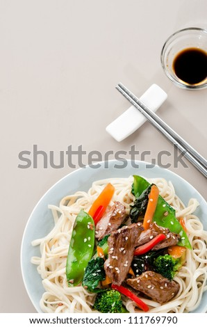 Stir fry beef asian chinese noodles with vegetables and soy dipping sauce, plenty of copy space - stock photo
