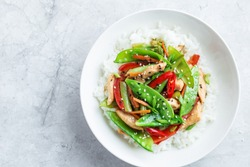 stir fry chicken and vegetables with rice in white bowl, top view