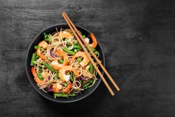 Stir fry noodles with shrimps and vegetables in black bowl.