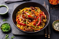 Stir fry noodles with vegetables and beef in black bowl. Slate background. Close up.