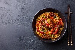 Stir fry noodles with vegetables and beef in black bowl. Slate background. Copy space. Top view.