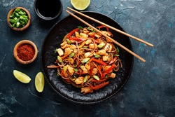 Stir fry noodles with vegetables and chicken in black bowl. Dark background. Top view. Copy space.
