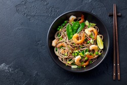 Stir fry noodles with vegetables and shrimps in black bowl. Slate background. Top view. Copy space.