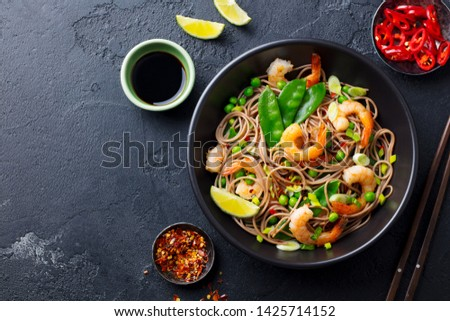 Stir fry noodles with vegetables and shrimps in black bowl. Slate background. Top view. Copy space. #1425714152