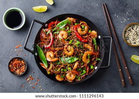 Stir fry noodles with vegetables and shrimps in black iron pan. Slate background. Top view.