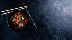 Stir fry soba noodles with beef and vegetables in wok on dark background, Asian udon noodles with beef WOK in black bowl on Slate background. Copy space
