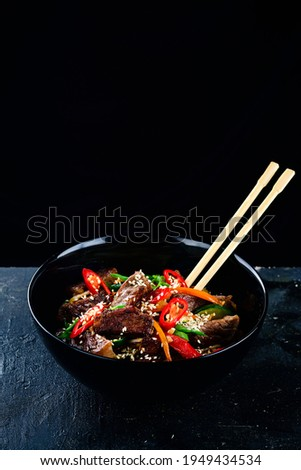 Stir fry soba noodles with beef and vegetables in wok on dark background, Asian udon noodles with beef WOK in black bowl on Slate background. Copy space Zdjęcia stock ©