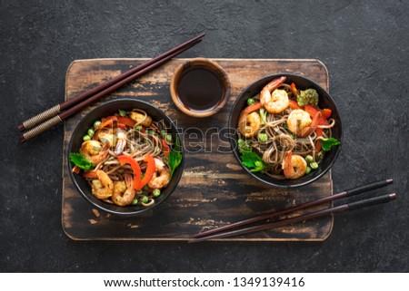 Stir fry with soba noodles, shrimps (prawns) and vegetables. Asian healthy food, stir fried meal in bowl on black background, copy space. #1349139416