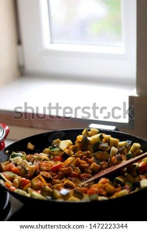 Stir frying seasonal vegetables in a wok. Chopped zucchini, tomato, eggplant and carrot, seasoned with turmeric. Selective focus.