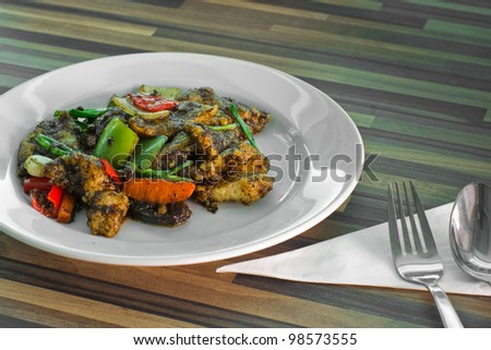 stired beef with colorful veggie on a wooden dining table.