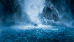 Stirling Falls plunging vertically over the cliff into Milford Sound, fanning out at its base in circular ripples on the surface of the water, New Zealand