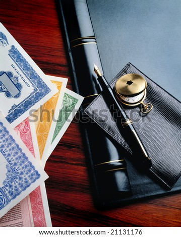 Stock certificates on desk with wallet and pen