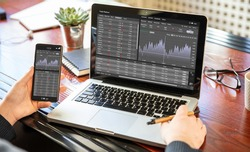 Stock exchange market analysis, Man working with a laptop, monitoring app on screen, office desk background. Trade platform, forex trading. Binary option, candlestick chart.