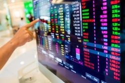 Stock exchange market business concept with selective focus effect. Display of Stock market quotes with finger pointing.