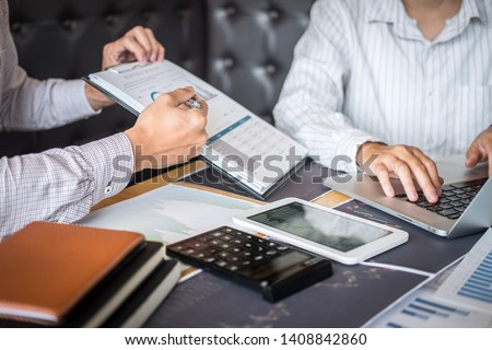 Stock exchange market concept, Team of investment trading or stock brokers having a consultation and analyzing with display screen and pointing on the data presented and deal on a stock exchange.