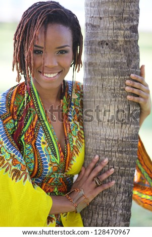 Stock image of a young black woman posing by a palm tree