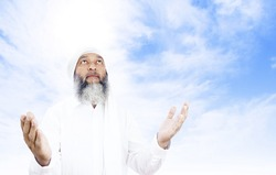 Stock image of Arabic man praying over open sky background