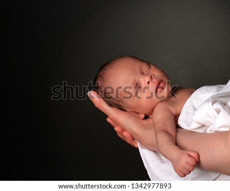 stock image of baby in mother's arms and wrapped up in white blanket just been cared for after having a good sleep in bed  stock photo