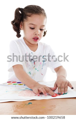 Stock image of child finger painting with watercolors over white background