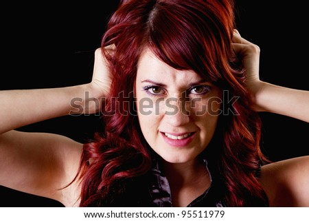 Stock image of frustrated female redhead over dark background