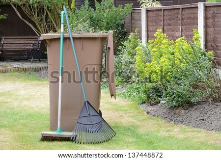 Stock image of garden waste in recycling container with lawn rake and sweeping brush in pleasant garden.