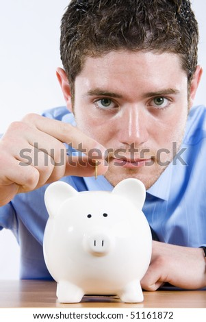 Stock image of man depositing coin into piggy bank