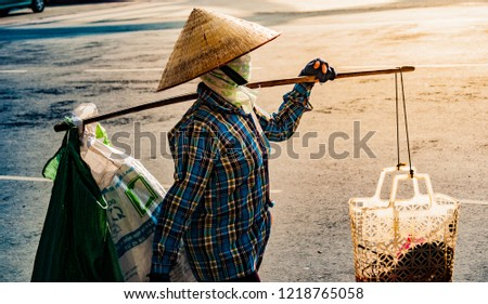Stock image of unrecognizable Vietnamese with conical hat carries a yoke on her shoulder along the street. Profile wiew of a human with conical hat in contrast sunset light.