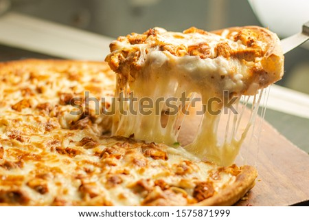 Stock image of Very cheesy pizza slice .Pizza is a savory dish of Italian origin, consisting of a usually round, flattened base of leavened wheat-based dough topped Stock photo ©