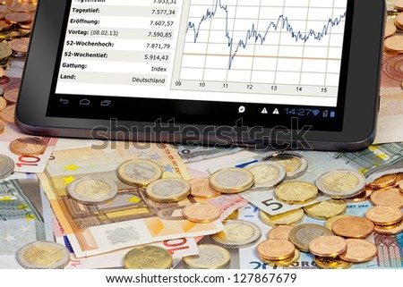 Stock index on Tablet PC with euro coins and bills