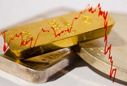 Stock market chart and close-up of gold bar on top of a silver ounce and coin