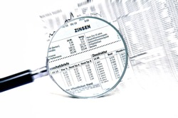 Stock market charts behind a magnifying glass