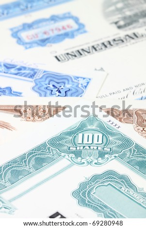 Stock market collectibles. Old stock share certificates from 1950s-1970s (United States). Vintage scripophily objects (obsolete) with shallow depth of field (focus on 100 shares).