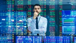 Stock Market Top Trader Looks at Projected Ticker Numbers and Graphs Running, Analysing Data to Make Best Sell. Behind Him Room Full of Screens and Statistics.