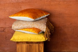 Stock of colorful pillows on wood chair against textured terracotta wall. Pile of soft yellow and orange cushions and blanket on stool near wall with space for text. Modern and cozy home concept.