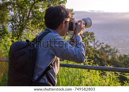 Stock Photo contributors tourism explore forests in Asia. hand holding camera holding pro digital camera with telephoto lens. Photo Stock career. Stock Photo contributors Concept lifestyle