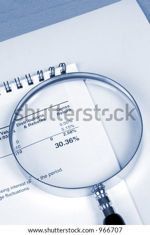 Stock Photo magnifier and paperwork illustrating gross return on investment of 30.36%. blue tone, genuine paperwork.