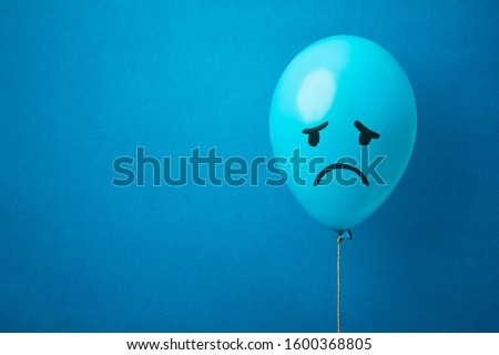 Stock photo of a blue balloon on a blue background with a sad face drawn. Blue monday concept
