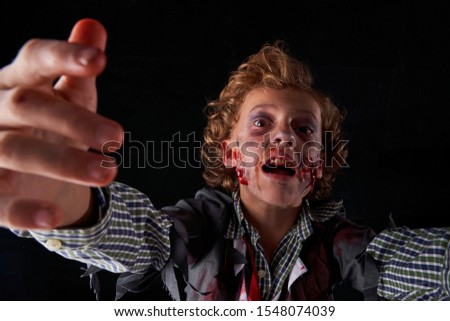 Stock photo of a boy disguised as zombie with blood and glitter with expression of fear. Halloween #1548074039